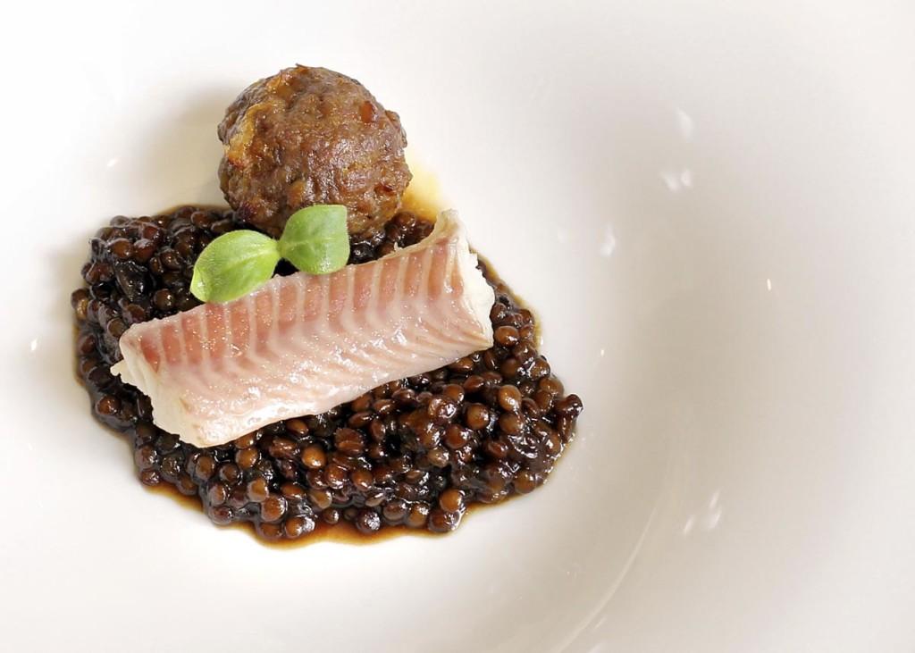 Anguila aumada y lentejas caviar en guiso con albondiguita a la naranja